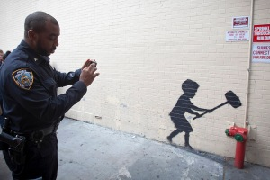 A police officer takes a photo of a new installation of British graffiti artist Banksy's art in New York