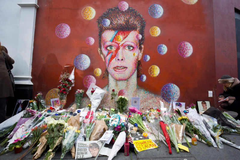 "Floral tributes are left beneath a mural of British singer David Bowie, painted by Australian street artist James Cochran, aka Jimmy C, following the announcement of Bowie's death, in Brixton, south London, on January 11, 2016. British music icon David Bowie died of cancer at the age of 69, drawing an outpouring of tributes for the innovative star famed for groundbreaking hits like ""Ziggy Stardust"" and his theatrical shape-shifting style. AFP PHOTO / JUSTIN TALLIS RESTRICTED TO EDITORIAL USE, MANDATORY MENTION OF THE ARTIST UPON PUBLICATION, TO ILLUSTRATE THE EVENT AS SPECIFIED IN THE CAPTION / AFP / JUSTIN TALLIS (Photo credit should read JUSTIN TALLIS/AFP/Getty Images)"