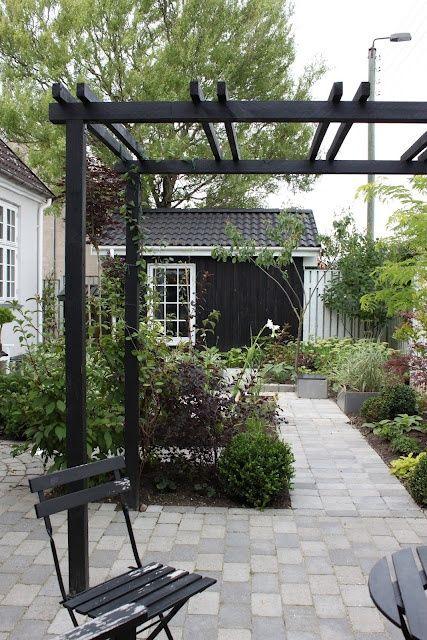 black pergola in garden